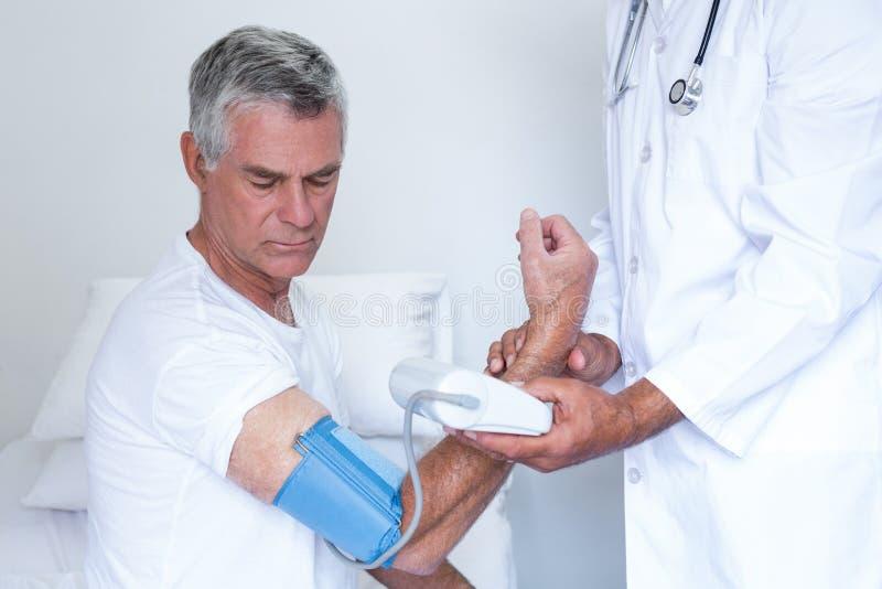 A verificação do doutor superior equipa a pressão sanguínea fotografia de stock