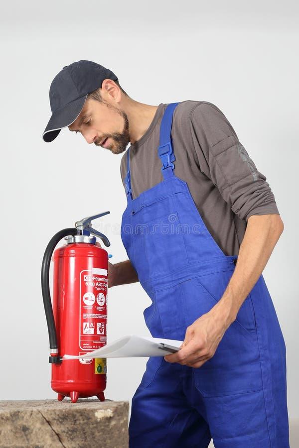 Verificação do extintor por um profissional foto de stock
