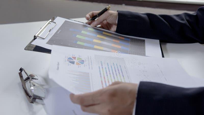 A verificação do homem de negócios analisa seriamente os colegas de um acionista do relatório da finança que discutem dados finan imagens de stock