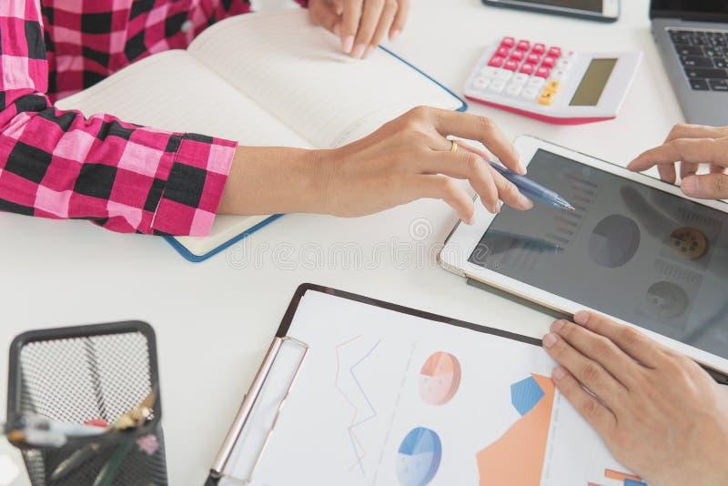 Verificação do homem de negócios sobre o custo e fazer o relatório do gráfico da finança no escritório imagem de stock royalty free