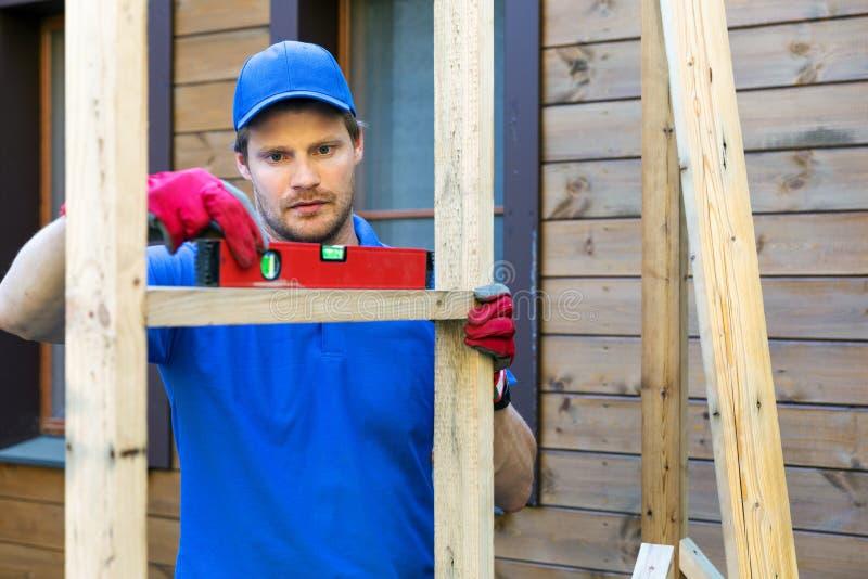 Verificação do trabalhador da construção o nível de quadro de madeira imagens de stock