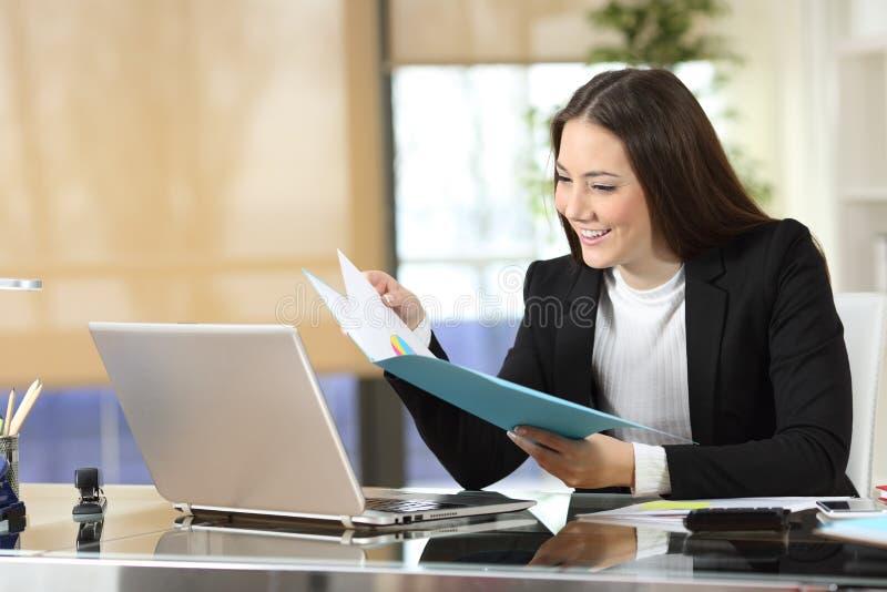 A verificação feliz da mulher de negócios informa no escritório imagem de stock royalty free