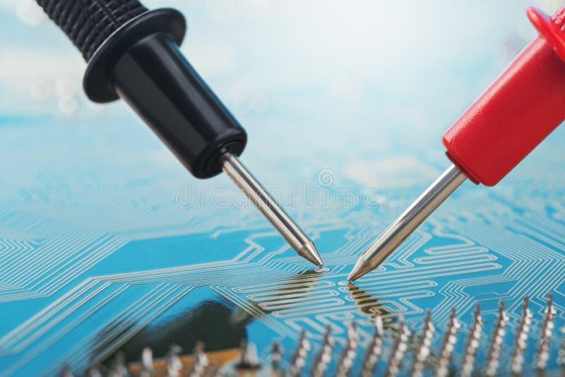 Verificação pelo multímetro, placa de circuito eletrônico do dispositivo digital com componentes Pesquisa de defeitos no disposit imagens de stock