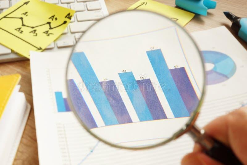 Verifica di affari L'uomo sta guardando tramite la lente d'ingrandimento sui grafici finanziari fotografia stock