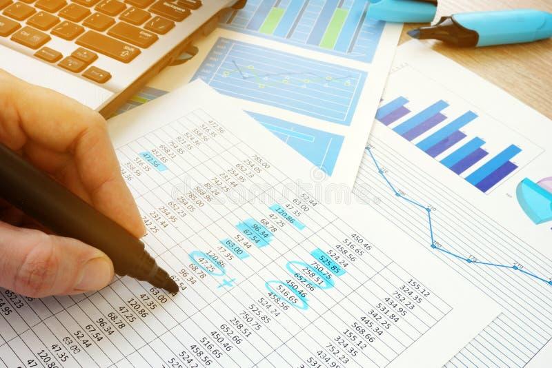 Verifica di affari Revisore dei conti che controlla i documenti con le figure finanziarie immagine stock