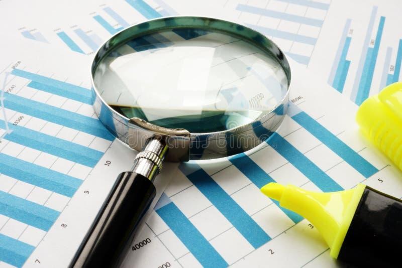 Verifica finanziaria e valutazione Lente d'ingrandimento e carte d'ufficio immagine stock