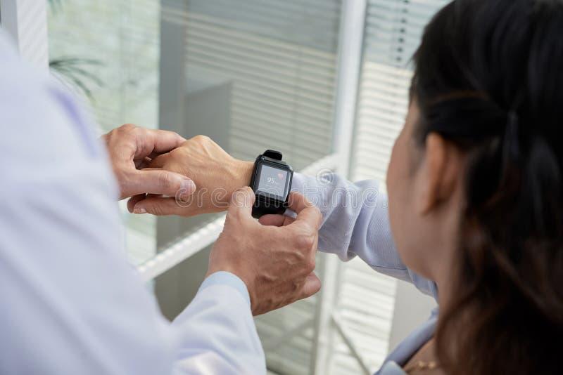 Verificando a frequência cardíaca com o Smartwatch foto de stock