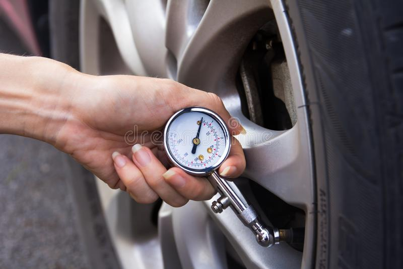 Verificando a press?o de pneum?tico do carro imagens de stock royalty free