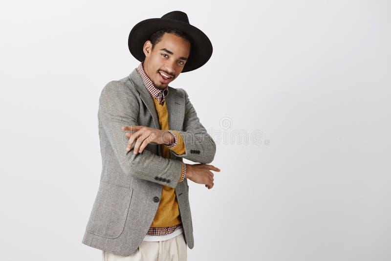 Verifique para fora meu equipamento novo Retrato do estudante masculino de pele escura seguro à moda no chapéu na moda, fazendo g foto de stock royalty free