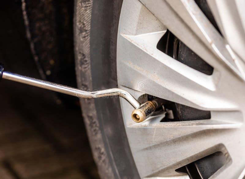 Verifique a pressão dos pneus no pneu de carro imagem de stock