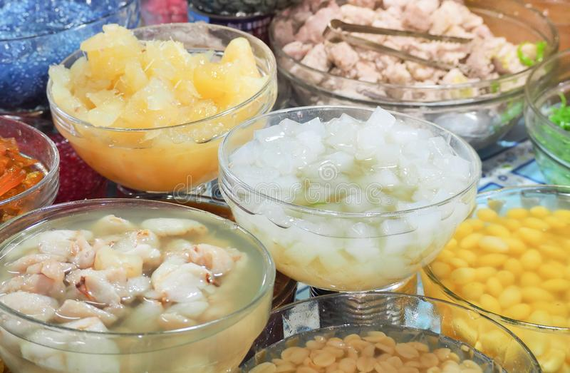 Verity sweet tropical fruit, corn, Logan , palm, coconut, cantaloupe and  taro with syrup in glass bowl. Thai dessert  ruam mit royalty free stock image