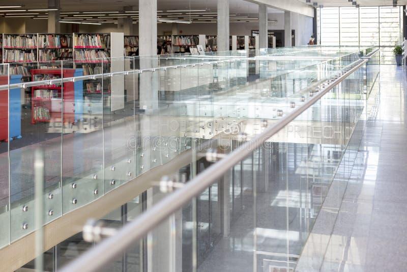 Verja de cristal en el pasillo por la biblioteca en universidad moderna foto de archivo