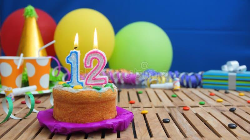 Verjaardag 12 cake met kaarsen op rustieke houten lijst met achtergrond van kleurrijke ballons, giften, plastic koppen en suikerg stock afbeelding