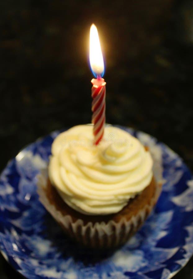 Verjaardag cupcake met één enkele aangestoken kaars stock afbeelding