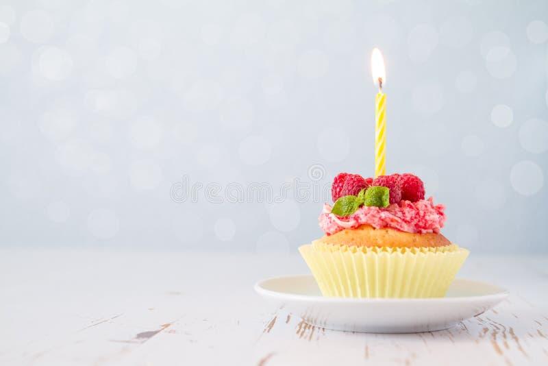 Verjaardag cupcake met framboos en suikergoed stock foto