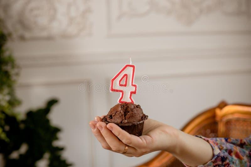 Verjaardag cupcake met genummerde kaars op witte achtergrond in vrouwelijke hand De geïsoleerde muffin met nummer vier op bovenka royalty-vrije stock afbeeldingen