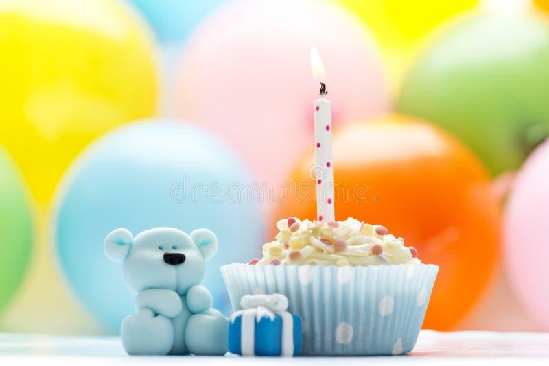 Verjaardag cupcake met teddy kaars en suiker stock afbeelding