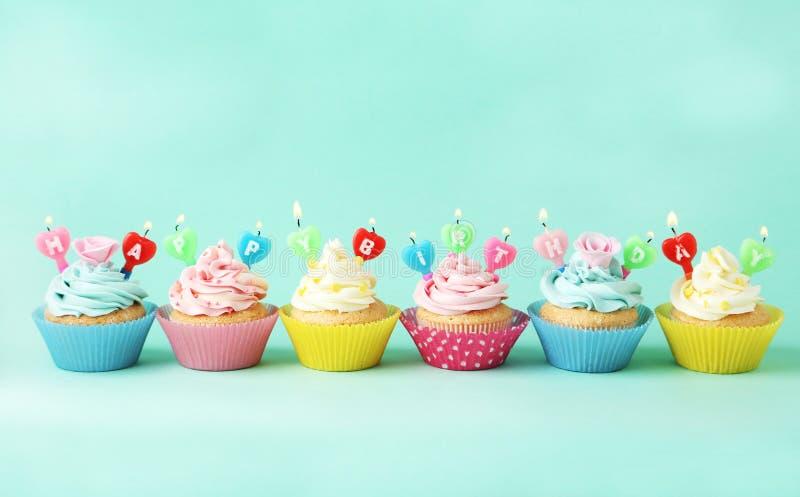 Verjaardag cupcakes met kaarsen op groene achtergrond royalty-vrije stock afbeeldingen