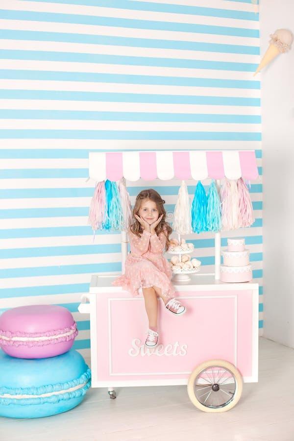 Verjaardag en gelukconcept - gelukkige meisjezitting op een karretje met roomijs en snoepjes tegen de achtergrond van een cand royalty-vrije stock foto's