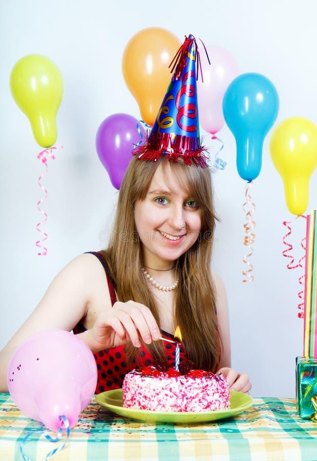 Verjaardag. Het gelukkige aantrekkelijke meisje steekt een kaars aan stock foto