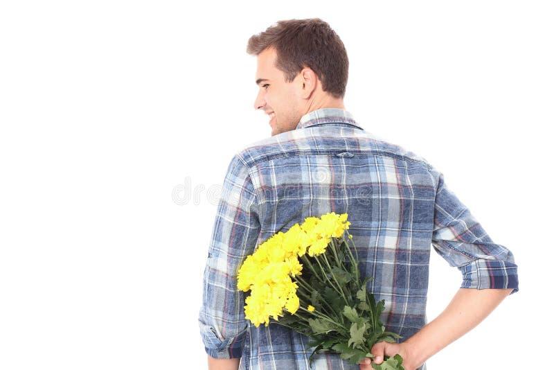 Verjaardag Knappe mens met geel die boeket van bloemen op wit wordt geïsoleerd Exemplaarruimte en spot omhoog Valentine-moederdag stock foto