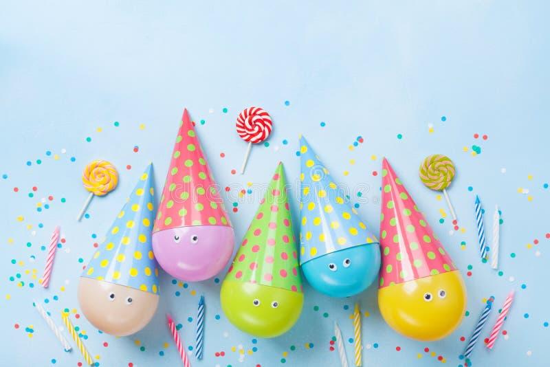 Verjaardag of partijachtergrond Grappige ballons, suikergoed en confettien op de blauwe mening van de lijstbovenkant Vlak leg De  royalty-vrije stock foto