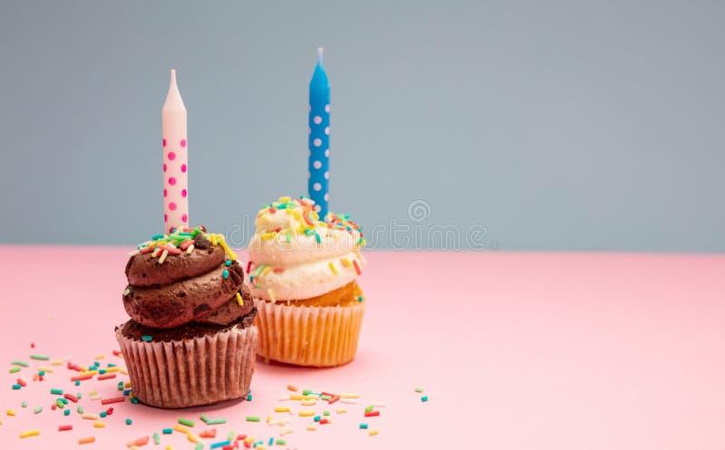 Verjaardag twee cupcakes met kaarsen op blauwe en roze pastelkleurachtergrond, exemplaarruimte stock foto's