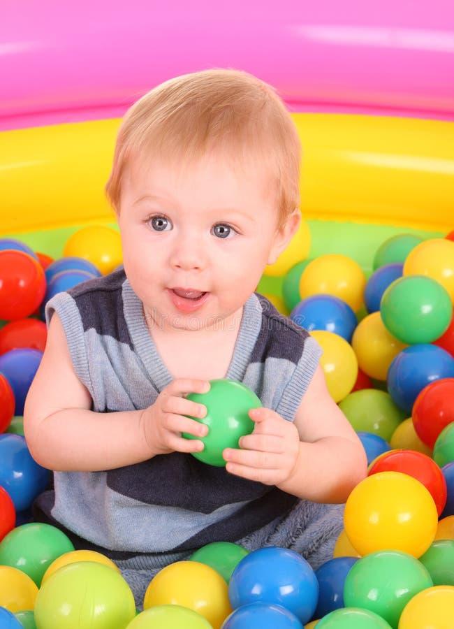Verjaardag van pretjongen in kleurenballen. stock foto's