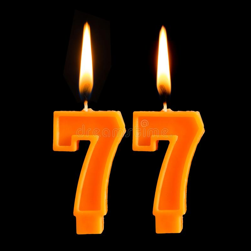 Verjaardags brandende kaarsen in de vorm van 77 die zevenenzeventig voor cake op zwarte achtergrond wordt geïsoleerd royalty-vrije stock foto's