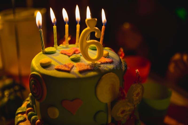 Verjaardagscake met het branden van kaarsen en leeftijd 6 kaars op de donkere achtergrond met suikergoed in decor royalty-vrije stock foto