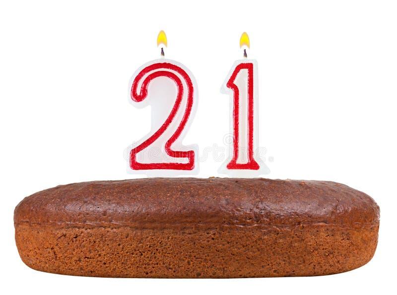 Verjaardagscake met kaarsen geïsoleerd nummer 21 stock foto