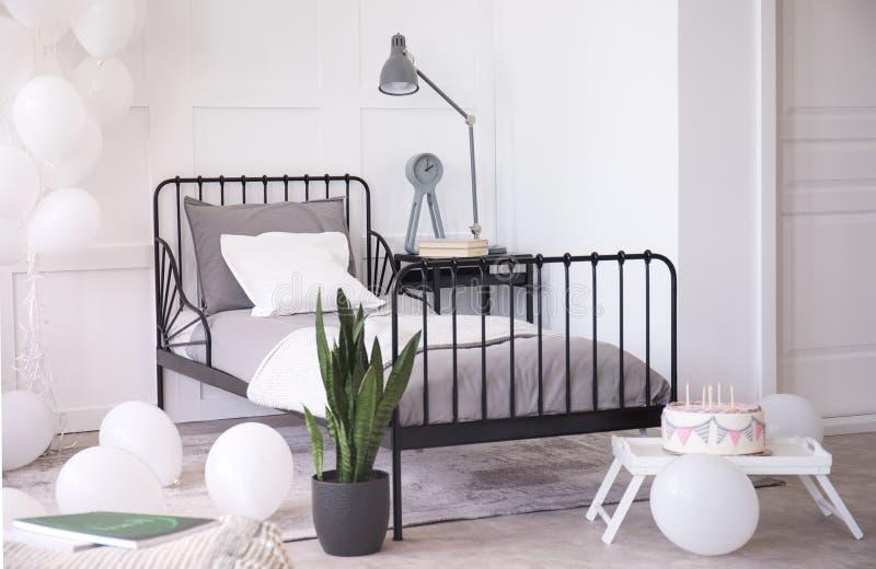 Verjaardagscake met kaarsen, groene installatie in zwarte pot en witte ballons in heldere elegante slaapkamer royalty-vrije stock foto