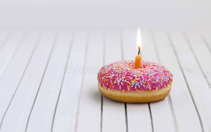 Verjaardagsdoughnut met roze glans en kleurrijk suikergoed en het branden royalty-vrije stock foto's