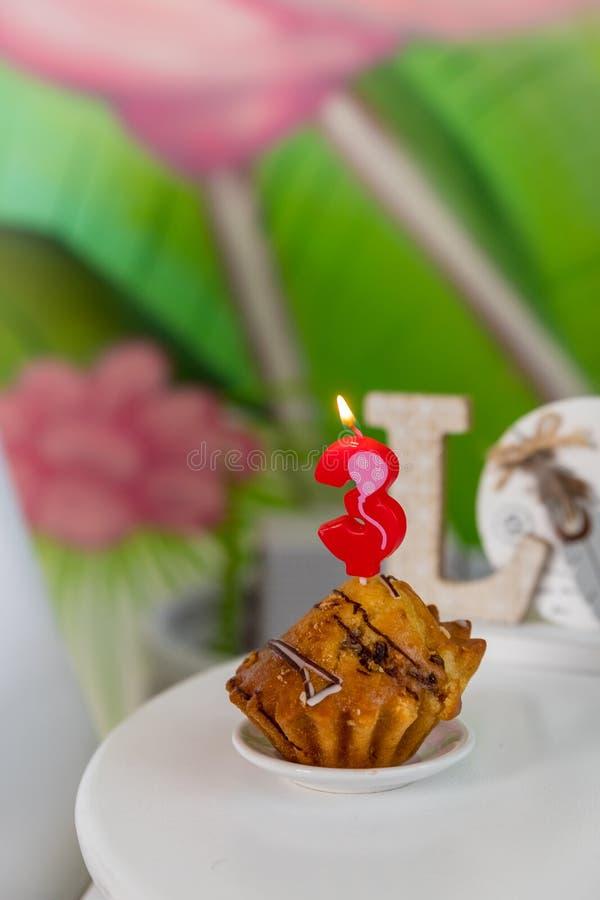 Verjaardagskaars in vorm van aantal in muffin Nummer drie verjaardagskaars op cupcake op een witte lijst Verjaardag cupcake stock foto