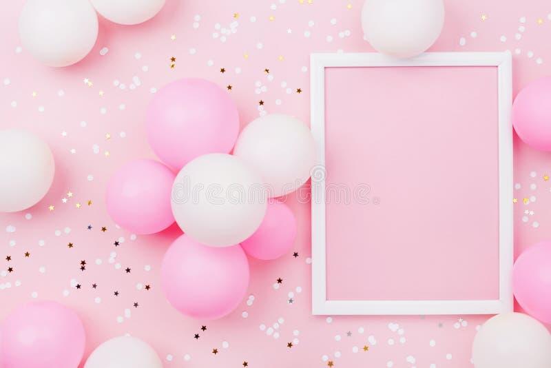 Verjaardagsmodel met kader, pastelkleurballons en confettien op de roze mening van de lijstbovenkant Vlak leg samenstelling royalty-vrije stock afbeeldingen