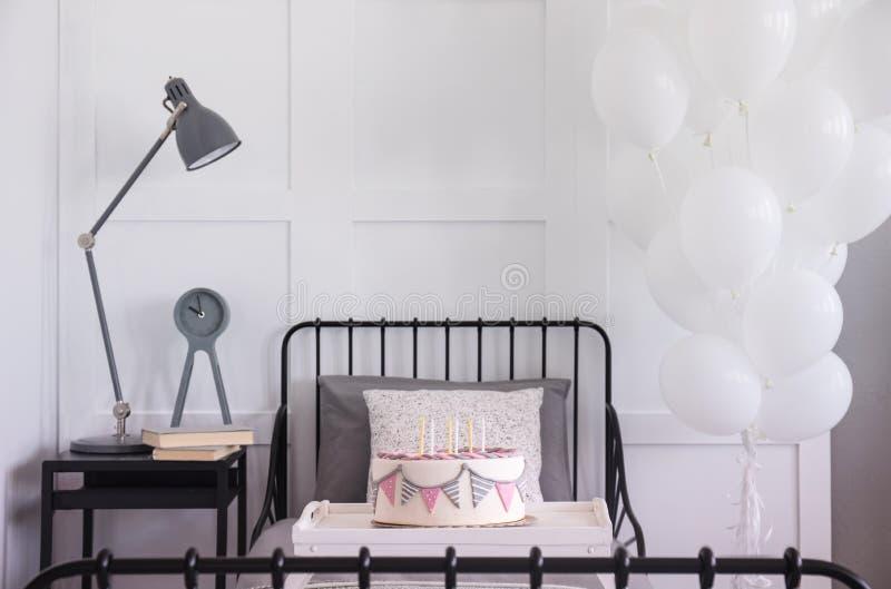 Verjaardagspartij in modern slaapkamerbinnenland met enig metaalbed, naast lijst met lamp, klok en boeken stock fotografie