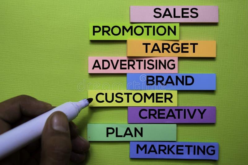 Verkäufe, Förderung, Ziel, Werbung, Marke, Kunde, Kreativität, Plan, vermarktender Text auf klebrigen Anmerkungen über grünen Sch lizenzfreies stockfoto