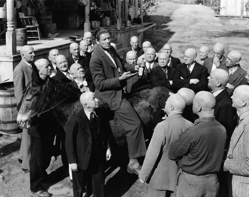 Verkäufer auf Esel mit Gruppe kahlen Männern (alle dargestellten Personen sind nicht längeres lebendes und kein Zustand existiert stockbilder
