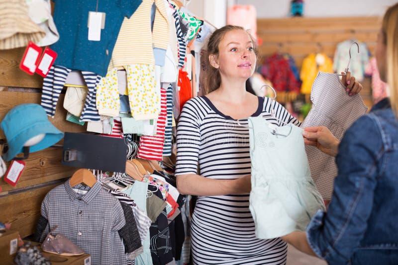 Verkäufer bietet Babykleid der schwangeren Frau im Kinderbekleidungsgeschäft an stockfotografie