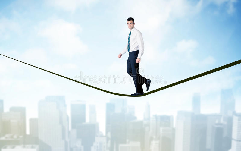 Verkäufer, der auf Seil über der Stadt geht stockfoto