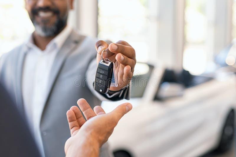 Verkäufer, der dem Kunden Neuwagenschlüssel gibt stockfotografie