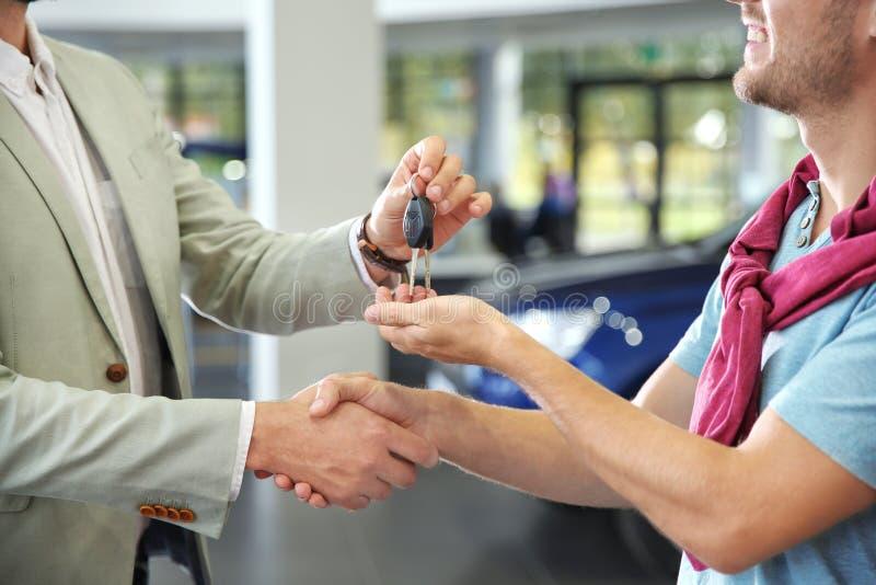 Verkäufer, der Hände mit Kunden beim Geben von Autoschlüsseln in der Verkaufsstelle, Nahaufnahme rüttelt lizenzfreies stockfoto
