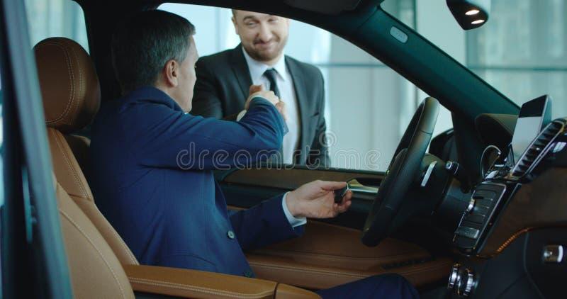 Verkäufer, der Hand zum Käufer innerhalb des Neuwagens rüttelt stockfoto