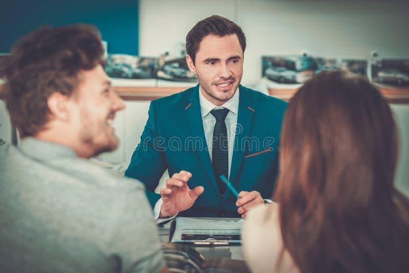 Verkäufer, der mit einem jungen Paar am Verkaufsstelleausstellungsraum spricht stockfoto