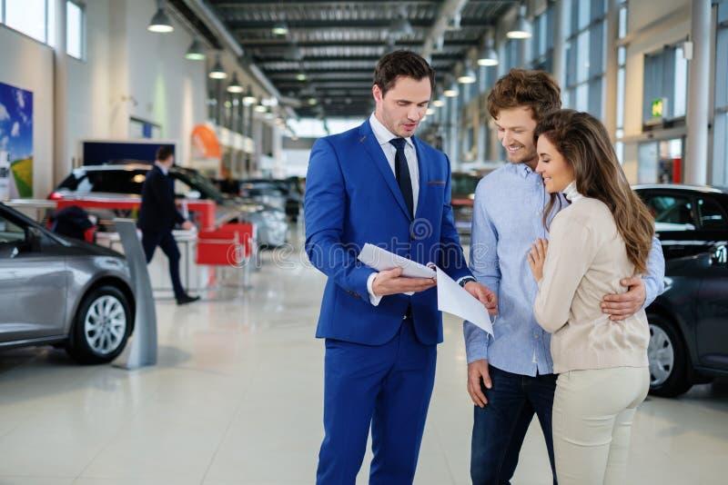 Verkäufer, der mit einem jungen Paar am Verkaufsstelleausstellungsraum spricht stockbild