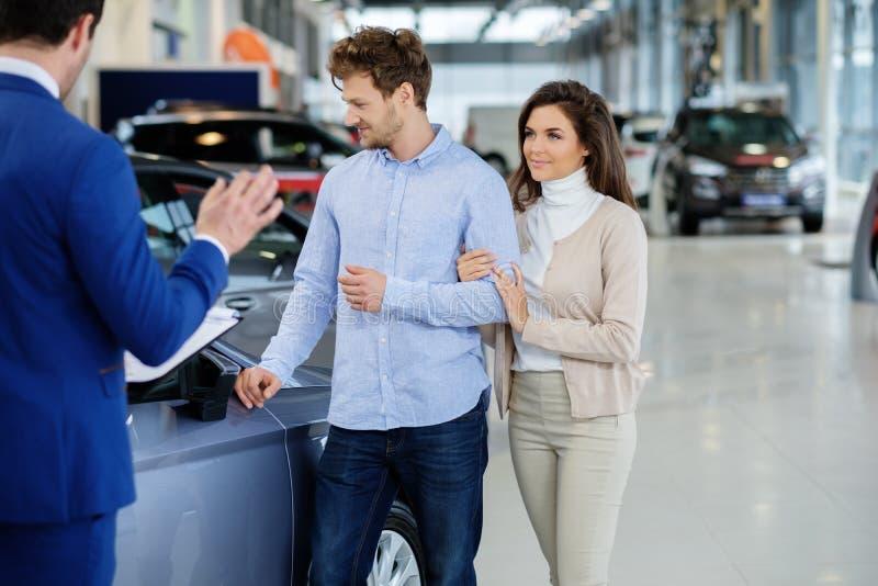 Verkäufer, der mit einem jungen Paar am Verkaufsstelleausstellungsraum spricht lizenzfreie stockfotos