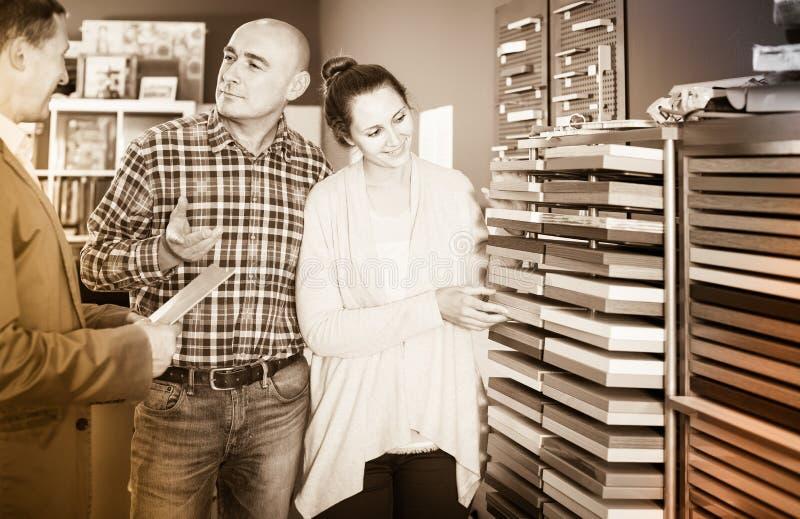 Verkäufer, der mit glücklichem Kunden im Speicher arbeitet lizenzfreies stockbild