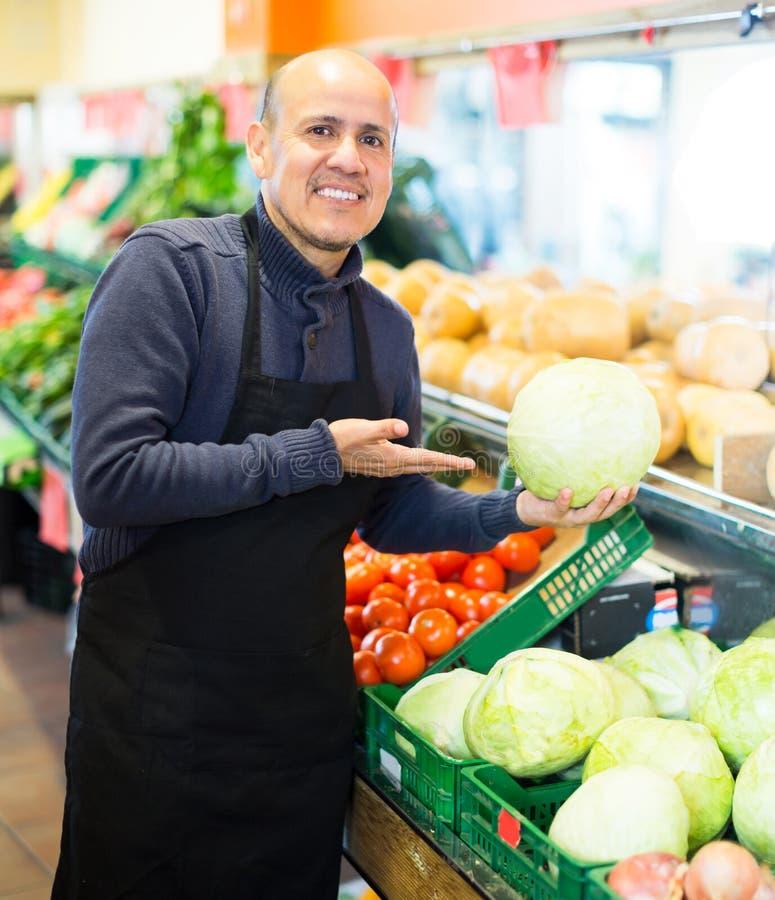 Verkäufer, der nahe unterschiedlichem Gemüse aufwirft stockfotos