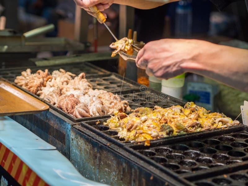 Verkäufer, der Riesen Takoyaki mit Käse am Shilin-Nachtmarkt macht lizenzfreie stockfotografie