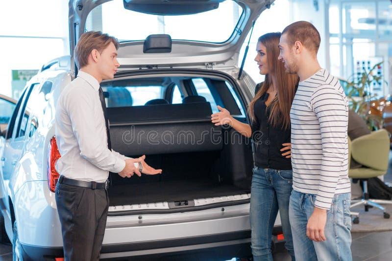Verkäufer, der Stamm des Autos zu den Kunden anzeigt stockbilder